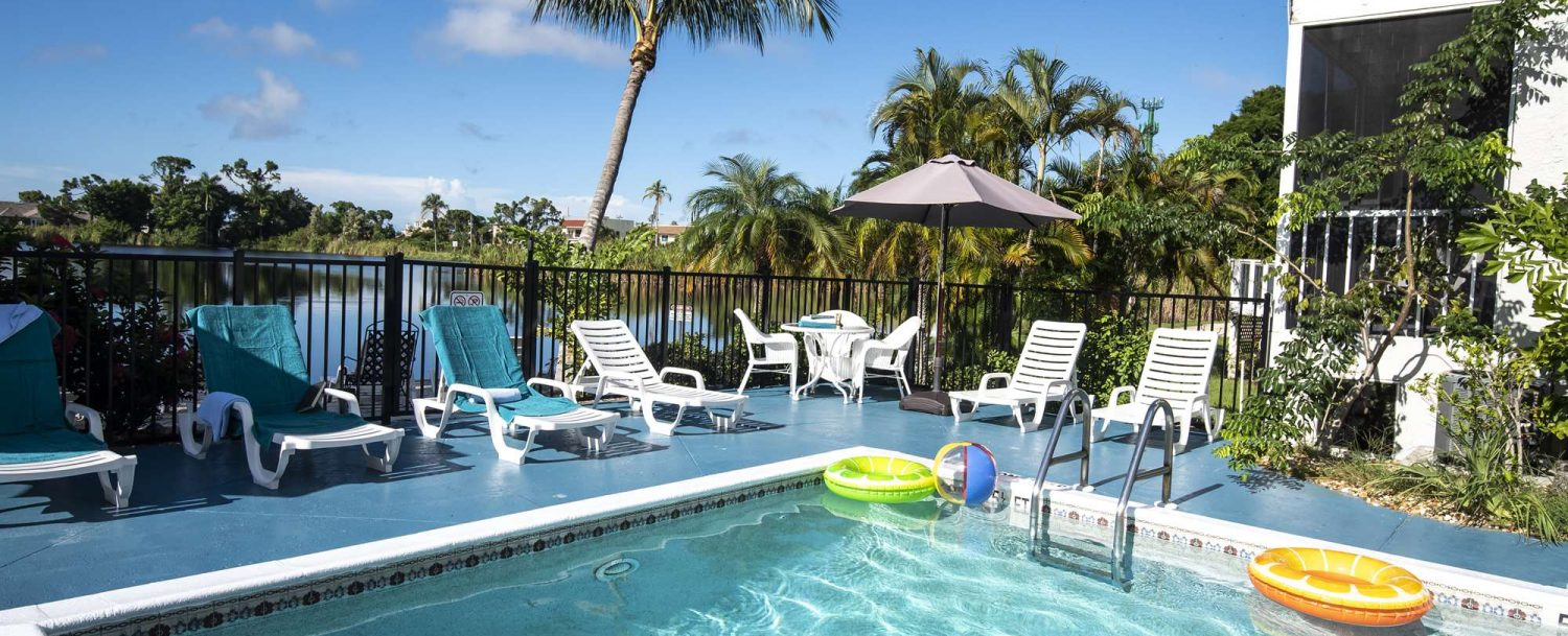 Marco Island Lakeside Inn exterior pool to table and umbrella