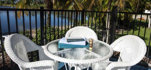 Marco Island Lakeside Inn exterior poolside table towels books lake